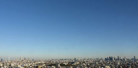 青空の広がる東京都内を一望する【池袋の高層ビル群(画面左、サンシャイン60などが見える))や新宿の高層ビル群(画面右、東京都庁なども見える)、また、サンシャイン60の右奥付近には東京スカイツリーも見える】