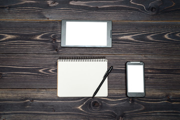 Office workplace with blank notebook (notepad), pen, tablet and smartphone with white screen on wooden table, copy space. Mock up template. Top view, flat lay. Business concept. View from above