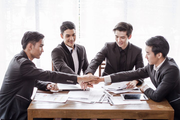 Group asia businessman together create a mutually beneficial business relationship. Economic graph on the table
