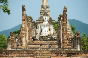 Sitting Buddha statue at the ruins of the main chapel of the Wat Mahathat temple in Sukhotai Historical Park, Thailand.