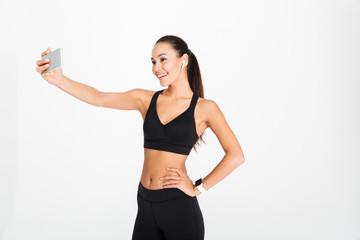 Portrait of a smiling asian fitness woman in earphones