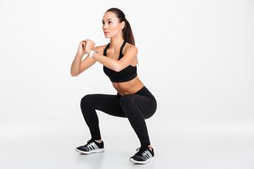 Portrait of a confident asian fitness woman doing squats