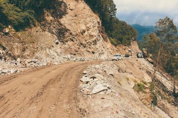 Muddy road and off-road vehicle on the way to Bumthang to Wangduephodrang.