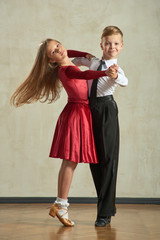 Attractive young couple of children dancing ballroom dance in studio