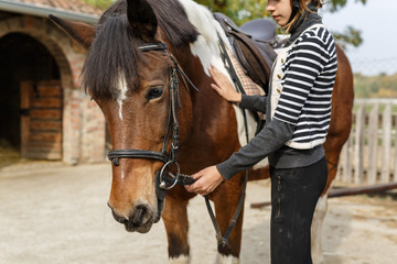 Ready for riding! -The girl holds her horse for reins