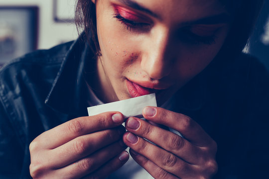 young beautifil girl with makeup licking cigarette paper