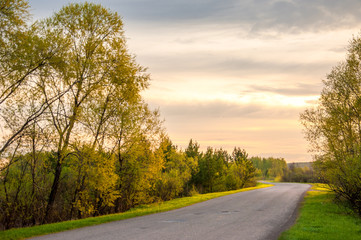 Spring landscape, sunrise sunrise. A country road, a rural landscape with a road.