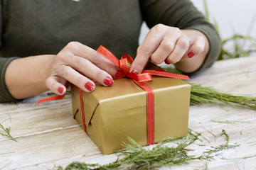 woman tying a red ribbon around a gift