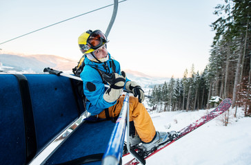 Close-up of skier man sitting at ski chair lift in the evening and looking at the camera with smile