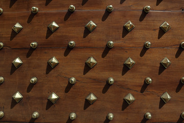 Wooden studded door, with gold studs.