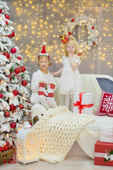 Merry Christmas and Happy Holidays Cute little child girls decorating the white green Christmas tree indoors with alot of presents wearing evening dresses with beautiful faces both