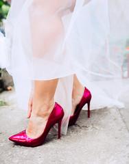 Bride in dark pink shoes on high heels