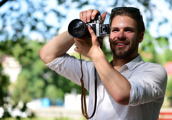 Guy with smiling face takes picture outside. Photographer holds camera