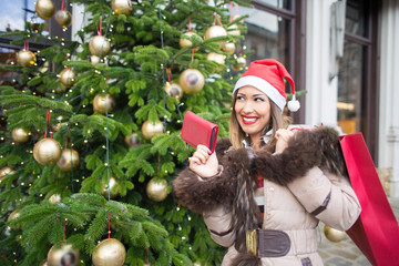 Beautiful woman christmas shopping with wallet