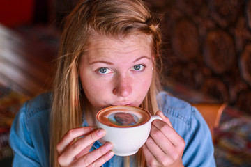 Young woman taking a sip of coffee with her face printed on.