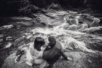 Groom in grey suit and bride in a light dress pose on the rocks before a mountain river
