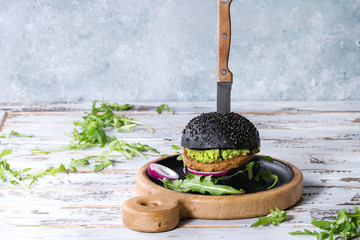 Homemade burger in black bun with avocado, arugula, onion on wood serving board over white wooden plank table. Rustic style. Homemade fast food.