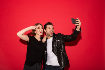 Cheerful punk couple posing and making selfie on smartphone