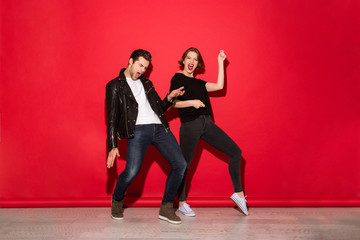 Full length image of playful punk couple dancing in studio