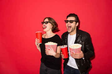 Happy punk couple in eyeglasses holding soda and popcorn