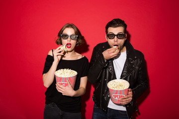 Surprised punk couple eating popcorn and looking at the camera