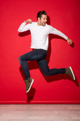 Full length image of happy man jumping and looking back