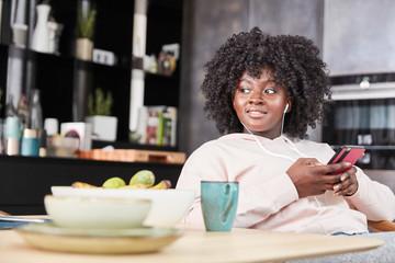 Afrikanische Frau mit Smartphone hört Musik