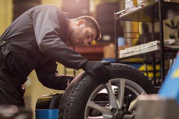 auto mechanic balancing car wheel at workshop Wall mural