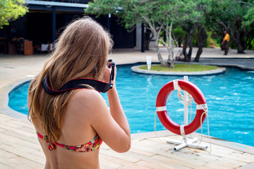 Back view of beautiful woman with dslr near pool