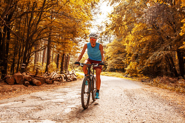 Young man riding a mountain bike on old country road.