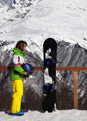 Young snowboarder with helmet in hands and snowboard on viewpoint in winter mountain