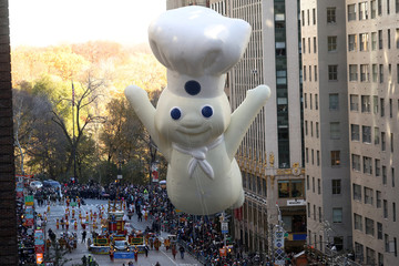 People take photos of the Pillsbury Dough Boy ballon as it takes part in the 91st Macy's Thanksgiving Day Parade in New York