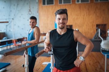 two smiling guys in oldschool wooden gym;