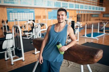 handsome guy has a break in oldschool gym;