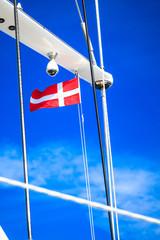Denmark flag on ship mast, blue sky in background