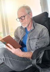 Portrait of mature man reading a book, light effect