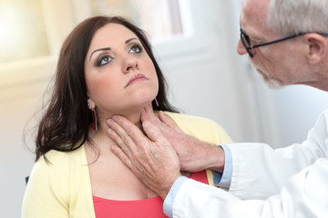 Doctor checking thyroid, light effect
