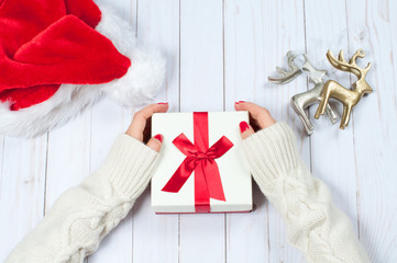 Woman holding Christmas gift on a wooden table background