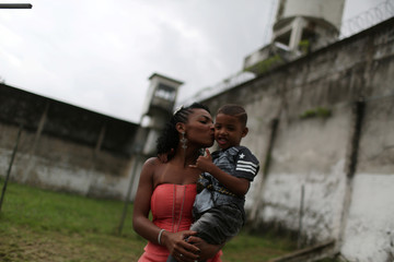 """A prisoner and participant of the """"TB Girl"""" beauty contest holds her son at the Talavera Bruce women prison in Rio de Janeiro"""