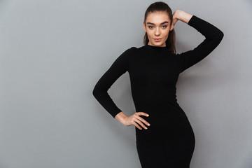 Portrait of a beautiful smiling woman in black dress posing