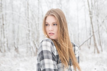 Young woman in black and white plaid shirt stading in a snow covered forrest.