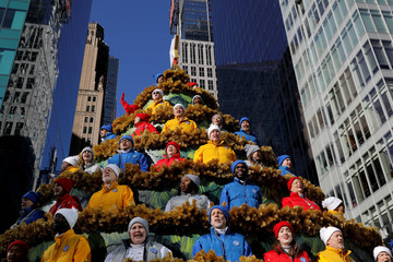 People sing carols in the Macy's Singing Christmas Tree on 6th Avenue during the Macy's Thanksgiving Day Parade in Manhattan, New York
