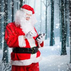 Weihnachtsmann checkt Tablet vor winterlichem Hintergrund