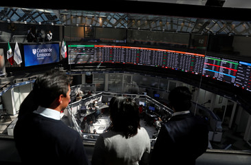 People look at screens displaying foreign exchange rates inside Mexico's Stock Exchange building in Mexico City