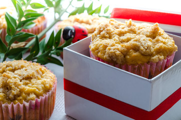 Homemade muffins packed in a box and tied with a red ribbon.