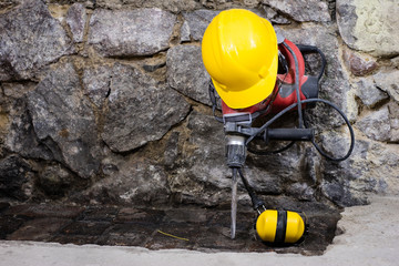 Construction tools for building a house on a stone wall. Hammer, helmet, and other necessary tools for construction or splitting.