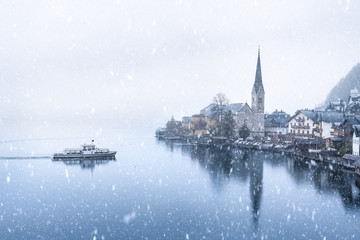 Hallstatt town and a boat under snowfall - Winter weather theme image with the famous touristic town, the Hallstatt, located on the Hallstatter lakeshore, in Austria, on a snowy day of November.