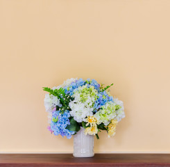 Bouquet in white ceramic jug on wooden table with cement yellow wall background