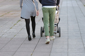 parents with a child in a stroller walk along the street