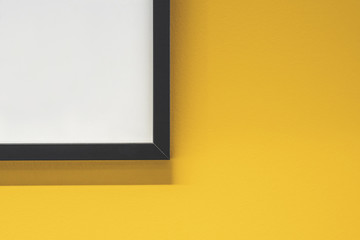 Black picture frame corner shot against a bright painted yellow wall.